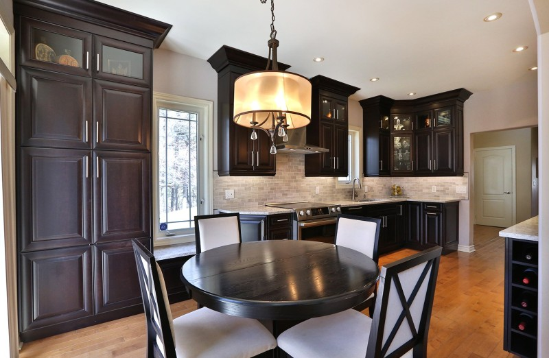 A modern kitchen with dark wood cabinets and hardwood flooring